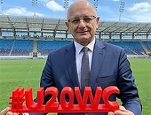 "Mayor Krzysztof Żuk standing on the Arena Lublin stadium holding ""#U20WC"" board"