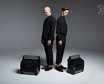 Two men dressed in black, standing in front of two accordions.