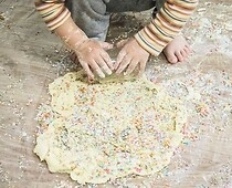 Hands of a child are kneading the dough.