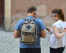 A woman and a man standing with an audio guide and in the background a tenement...